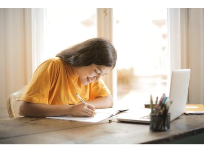 A girl in a yellow shirt studies at a home computer